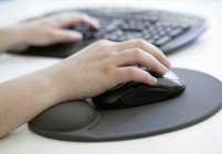 GERMANY, BONN, Health at work, Our picture shows a hand with computer mouse on an ergonomic mousepad with built-in wrist rest made of silicone gel before a computer keyboard.
